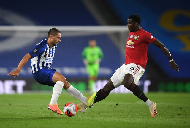 Brighton's Neal Maupay, left, and Manchester United's Paul Pogba battle for the ball