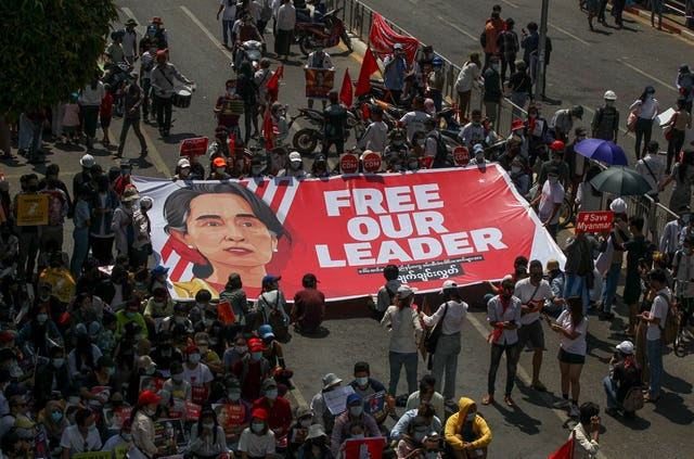 Demonstrators display a banner with an image of deposed Myanmar leader Aung San Suu Kyi (AP)