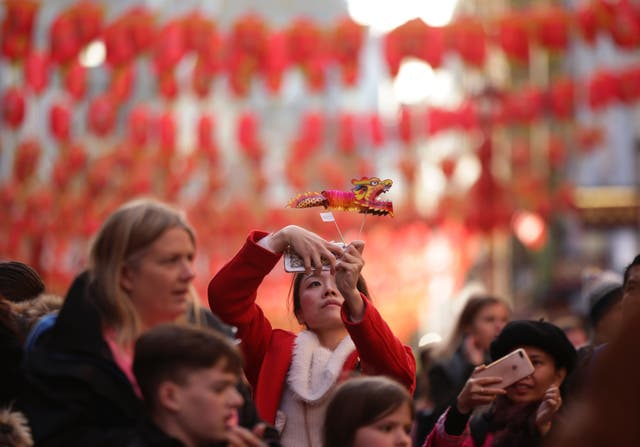 A woman takes a selfie against a backdrop of hanging lanterns in Gerrard Street in Chinatown, London (Yui Mok/PA)