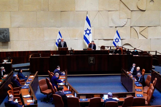Benny Gantz, at the podium, speaks at the Knesset