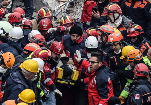 Rescue workers carry a 16-year-old boy  from the rubble