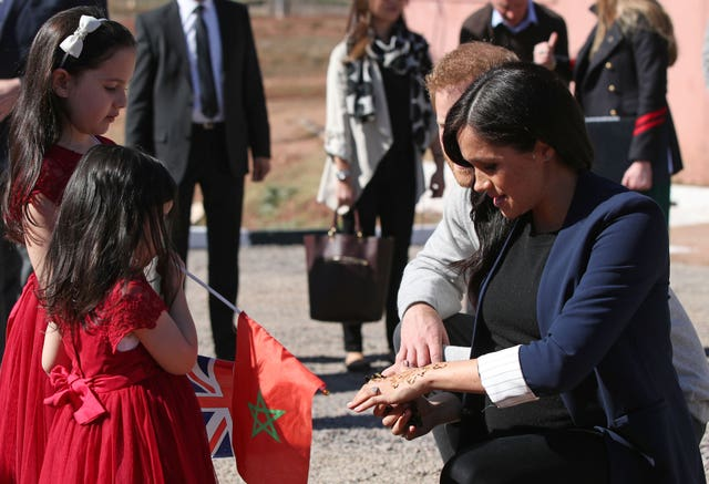 The Duchess of Sussex shows two girls her henna design