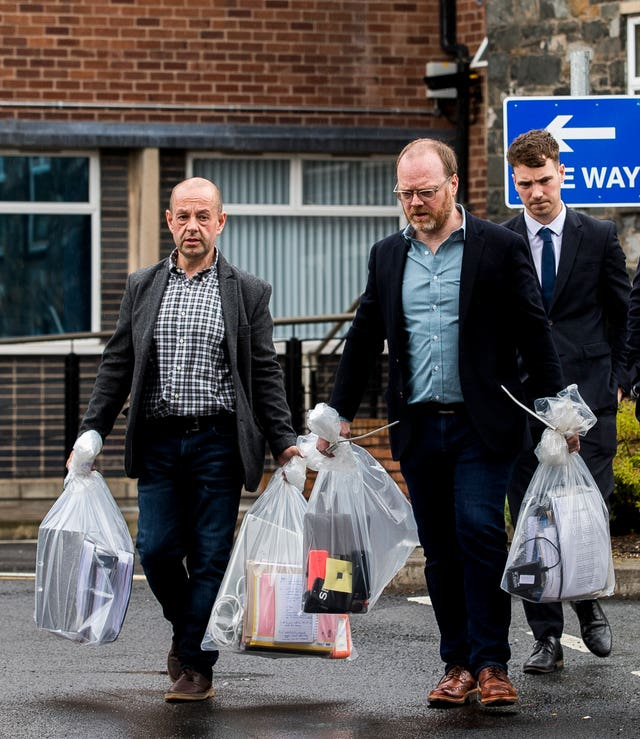 Barry McCaffrey and Trevor Birney carry away their returned documents