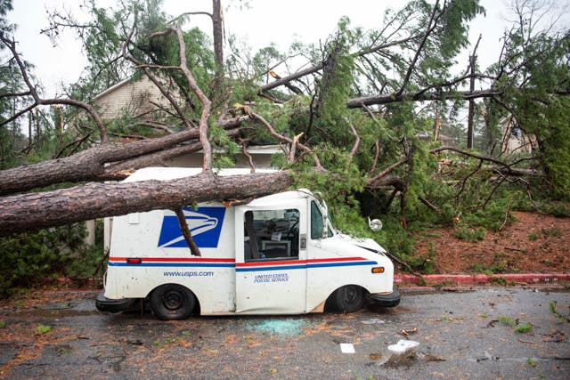 Fallen trees rest on a damaged postal truck at an apartment complex where a reported tornado passed through in Spartanburg, South Carolina