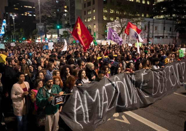 "Demonstrators march holding a banner with a message that reads in Portuguese: ""The Amazon belongs to the people"""