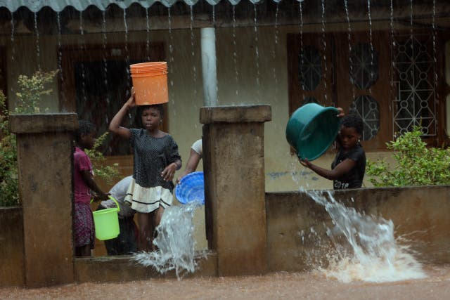 A family scoop water from their flooded home, in Natite neighbourhood in Pemba