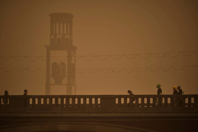 People walk across a bridge in a cloud of red dust