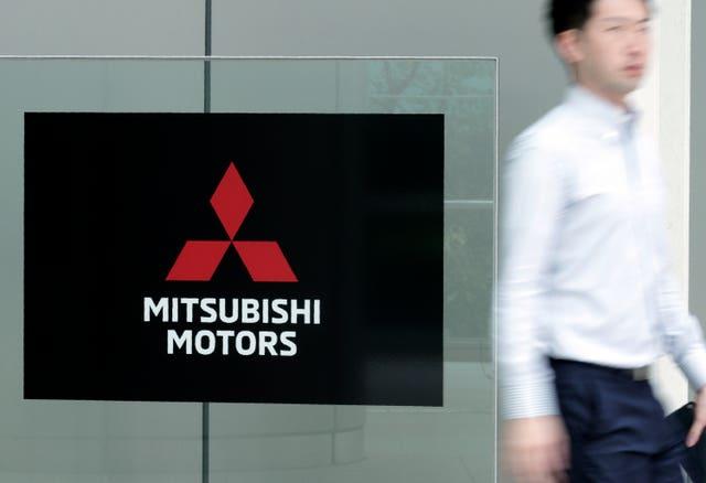 A man walks past Mitsubishi Motors headquarters in Tokyo