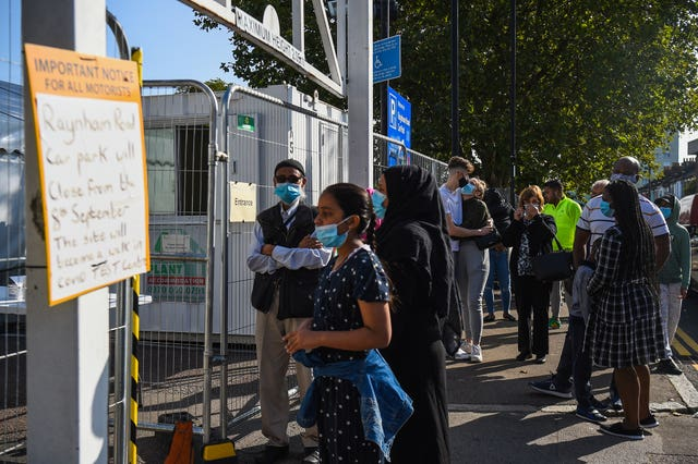 People queue outside a coronavirus testing centre offering walk-in appointments in north London