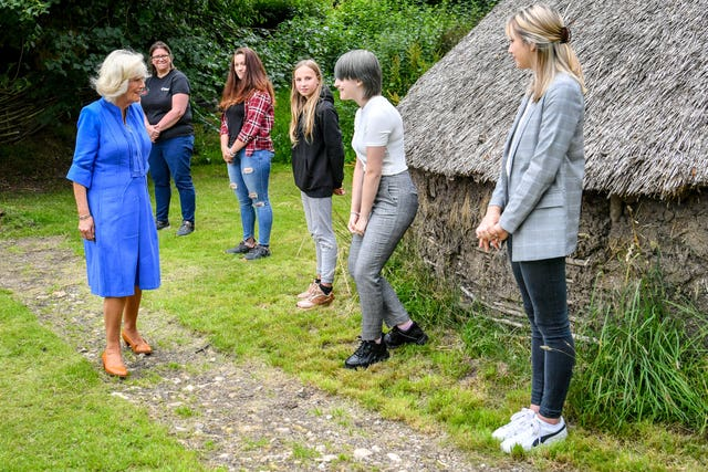 Young carer Allanna O'Brien curtseys as she meets the Duchess of Cornwall during a visit to the Youth Action Wiltshire Oxenwood Outdoor Activity Centre near Marlborough, Wiltshire