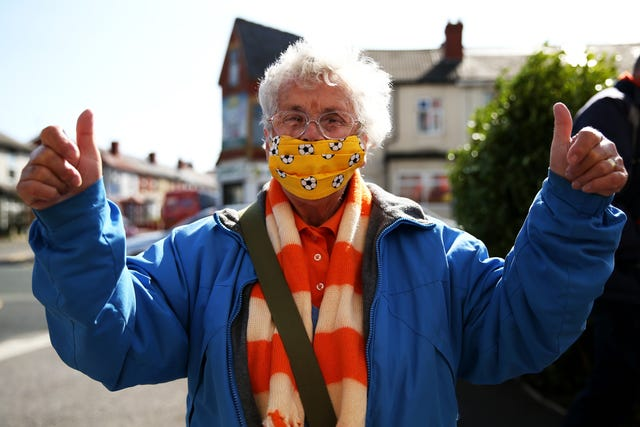 A Blackpool fan wearing a football patterned face mask poses on the way into the League One match against Swindon