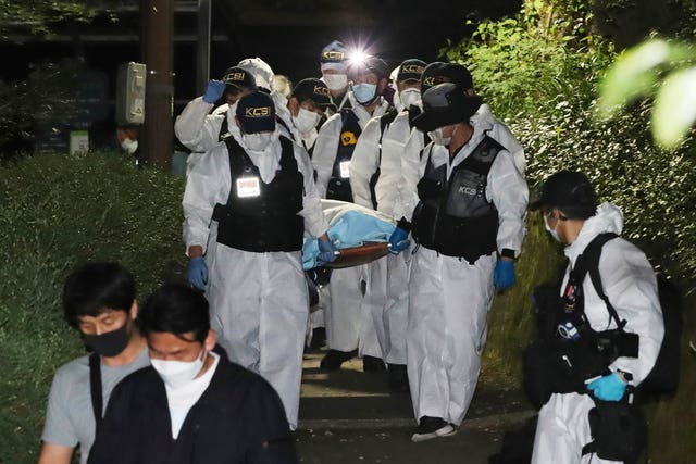 Police officers carry the body of Mr Park