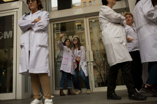 Medical personnel stand outside La Princesa hospital during a protest in Madrid (Francisco Seco/AP)