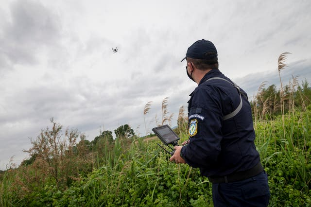 Police drone operator Thanassis Kyriakidis flies a drone while patrolling the Evros River near the village of Feres on the Greek-Turkish border in Greece