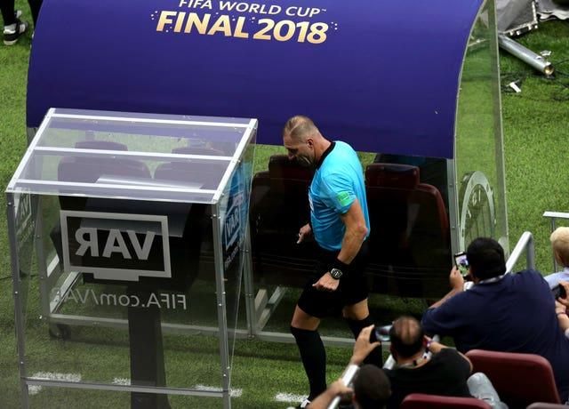 Nestor Pitana checks the monitors during the 2018 World Cup final between France and Croatia