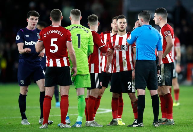 Declan Rice (far left) awaits the result of a VAR check after West Ham's injury-time equaliser was called into question and eventually disallowed due to a handball