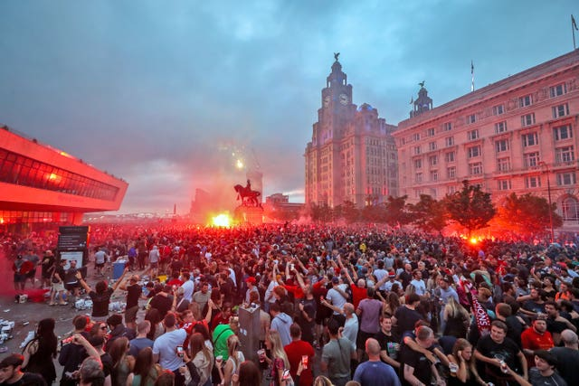 Liverpool fans let off flares outside the Liver Building