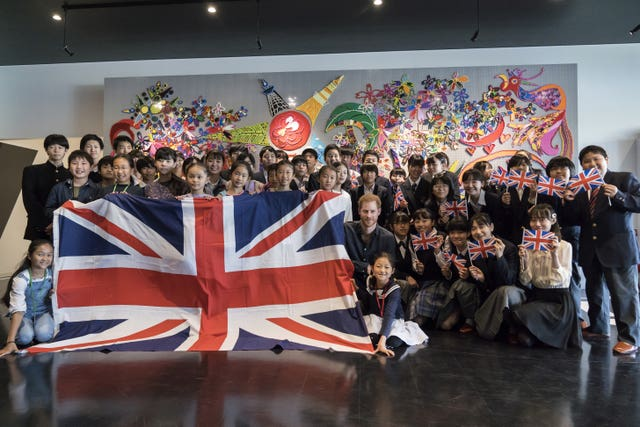 The Duke of Sussex poses with students at the Nippon Foundation Para Arena in Tokyo
