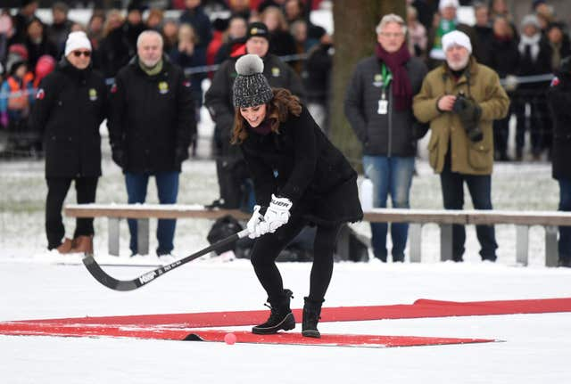 The Duchess of Cambridge hits a hockey ball as she and the Duke of Cambridge meet a group of local bandy hockey players