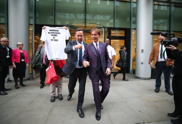 Sir Cliff Richard, right, leaves the Rolls Building in London, where a High Court judge was hearing evidence (Yui Mok/PA)