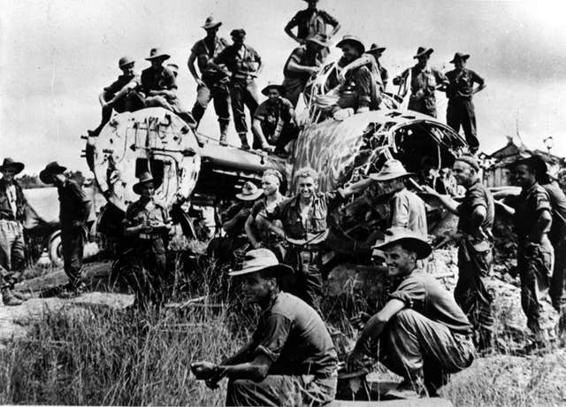 Members of the battalion from the Australian 9th Division climb over a wrecked Japanese bomber abandoned on the edge of the strip in Borneo