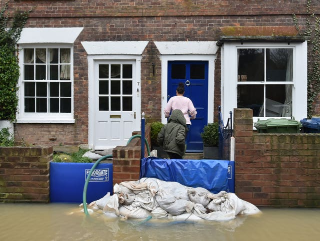 A woman and child enter a flood-hit cottage