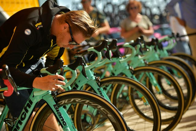A member of Team Jumbo-Visma's staff checks the brake of a bicycle during the 14th stage of the Vuelta a Espana