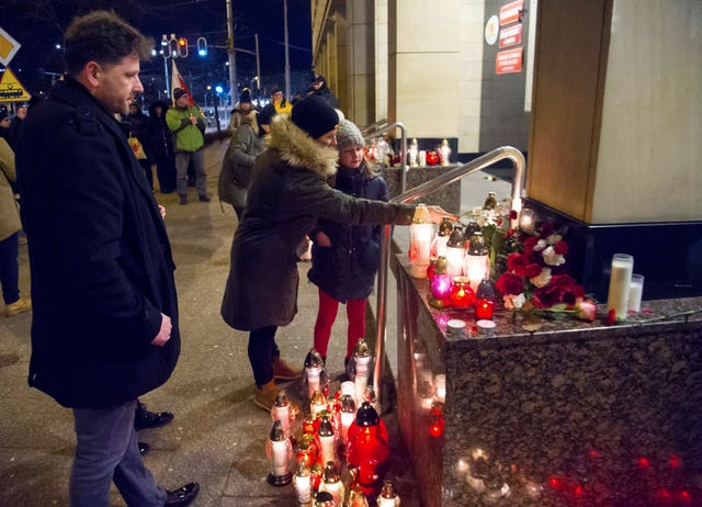 People place candles as they mourn Pawel Adamowicz in Gdansk