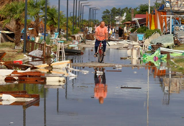 A man rides a bicycle among debris after a storm at Nea Plagia village in the Halkidiki region of northern Greece
