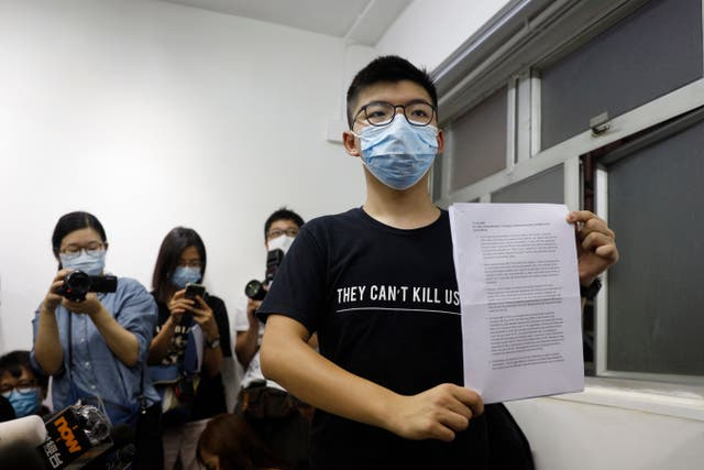 Hong Kong pro-democracy activist Joshua Wong shows his disqualification notice during a press conference (Kin Cheung/AP)