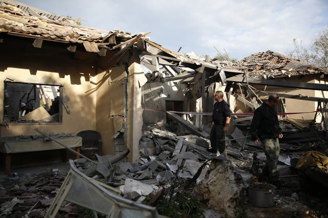 Police officers inspect the damage to a house hit by a rocket in Mishmeret, central Israel