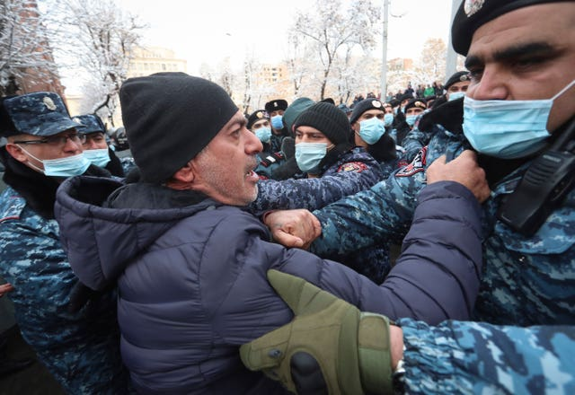 Armenian police officers detain a demonstrator (Vahram Baghdasaryan/AP)