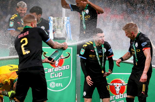 Manchester City's Kyle Walker, left, sprays Alexander Zinchenko, right, and Phil Foden with Champagne