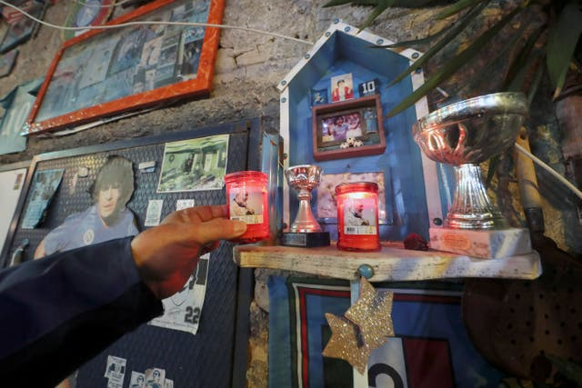 A man in Naples places a candle of St Padre Pio in a makeshift shrine to Diego Maradona