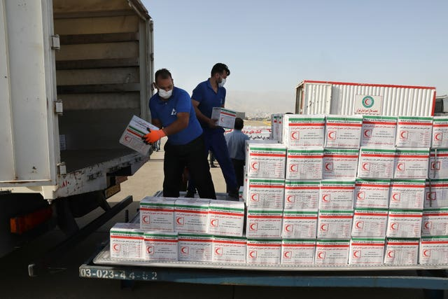 Workers in Iran unload boxes of aid supplies from a lorry to load on to a plane bound for Beirut, Lebanon (Vahid Salemi/AP)