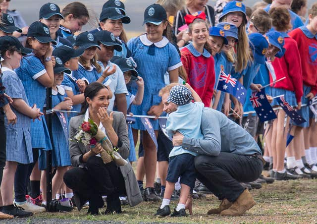 Harry and Meghan greet a youngster in Australia