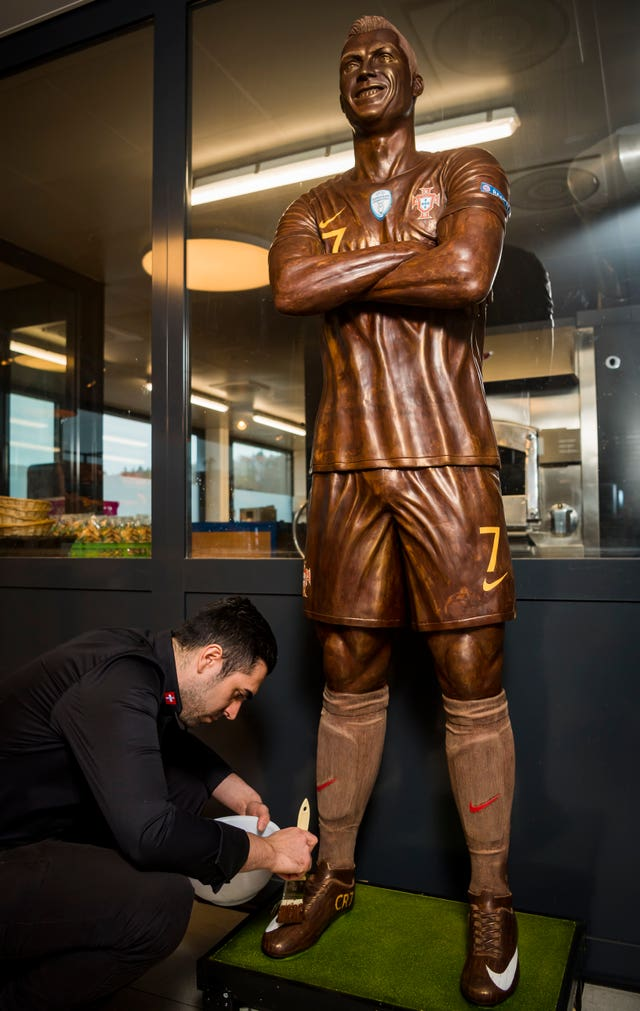 Portuguese chocolatier Jorge Cardoso applies the finishing touches to a chocolate model of football star Cristiano Ronaldo at the Suard chocolatier factory in Givisiez near Fribourg, Switzerland