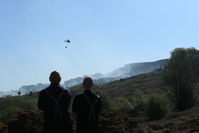 Firefighters use a helicopter to drop water on Ilkley Moor