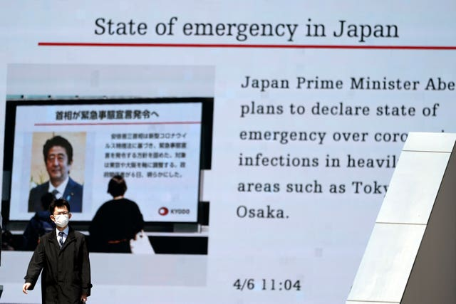 A man walks past a screen showing the news report that Japanese Prime Minister Shinzo Abe plans to declare a state of emergency over coronavirus in Tokyo