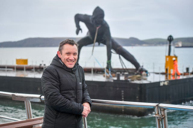 Artist Joseph Hillier on a boat beside his sculpture Messenger