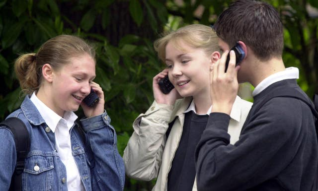 Children using mobile phones. Excessive screen time has been linked to lower levels of happiness in teenagers (Tim Ockenden/PA Images)