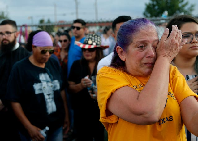 Cathe Hill wipes tears from her eyes during a vigil for victims of Saturday's mass shooting at a shopping complex in El Paso, Texas