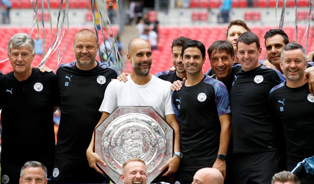 Pep Guardiola, centre, clutches the Community Shield