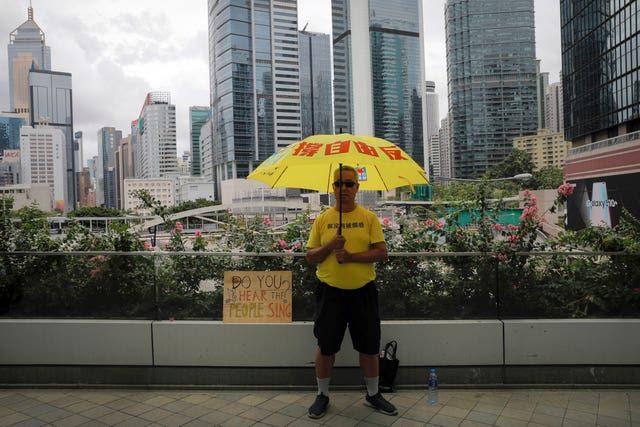 A man holds an umbrella outside the Legislative Council