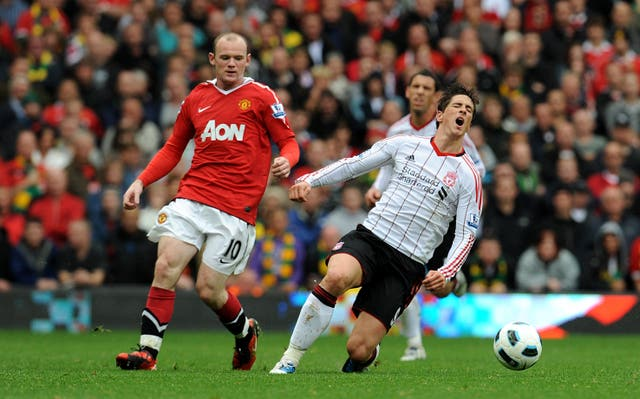 Torres goes to ground after a challenge by Manchester United's Wayne Rooney at Old Trafford in September 2010