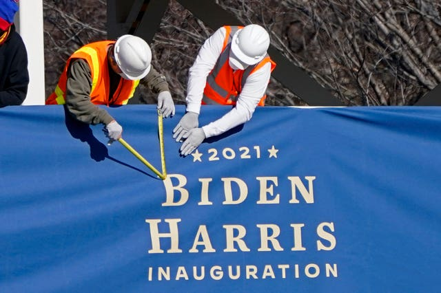 Workers put up bunting on a press riser for the upcoming inauguration of President-elect Joe Biden and Vice President-elect Kamala Harris (Gerald Herbert/AP)