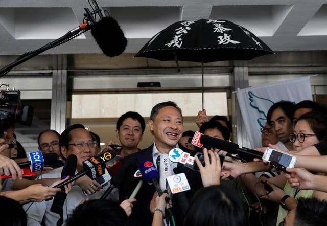 Benny Tai talks to reporters outside the court