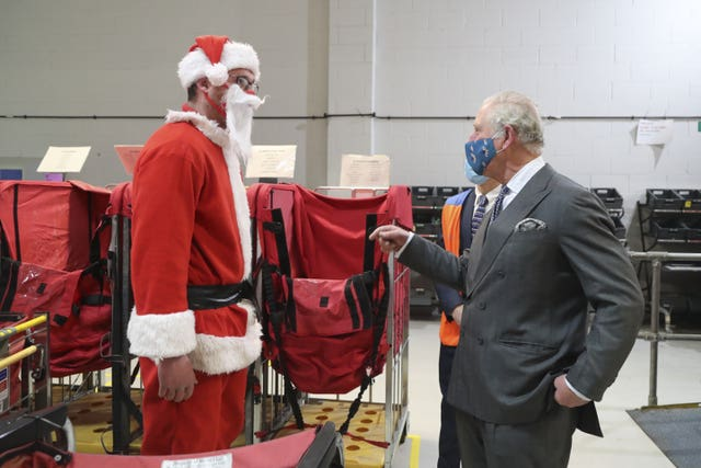 Charles speaks to postal worker Tim Lafford dressed in a Father Christmas outfit. Geoff Caddick/PA Wire