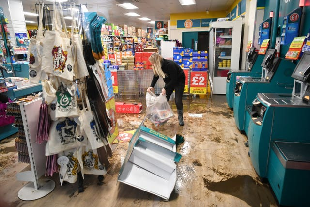 An employee cleans a Poundland shop hit by flooding in Pontypridd