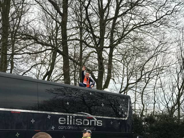 A Blackpool fans sits on the Arsenal team bus